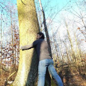 Abbracciare gli alberi fa bene alla salute, lo dice la scienza. Un uomo abbraccia un albero in un bosco.