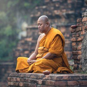 VIVERE SECONDO L'IDEALISMO DEL BUDDISMO ZEN. Un monaco prega su un'altura rocciosa, indossa la classica tunica arancio da monaco.