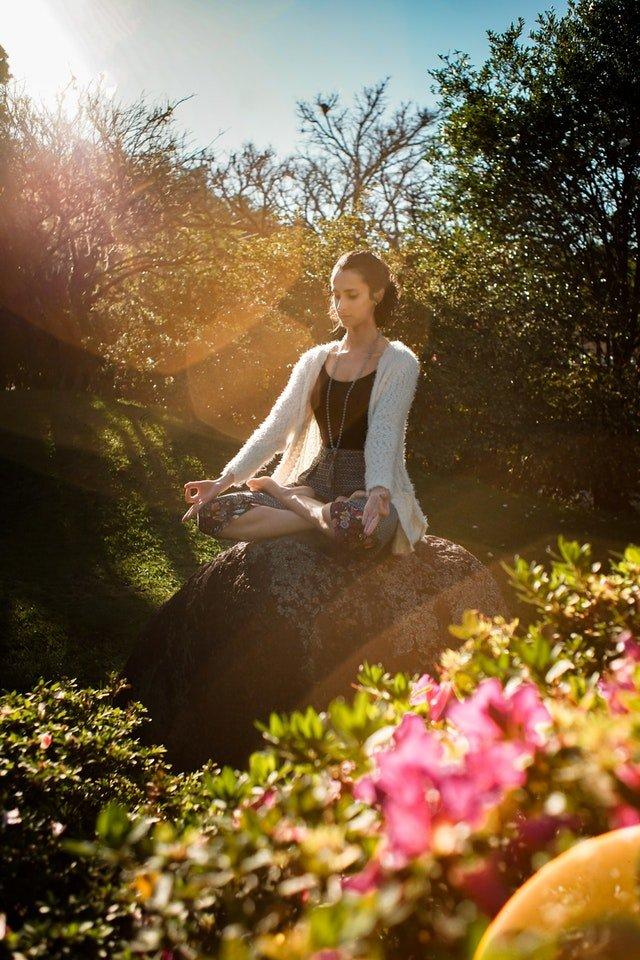 I 4 ELEMENTI PER REINVENTARE IL PROPRIO CORPO NELLA FORESTA. Nella foto una ragazza medita nel bosco sugli elementi