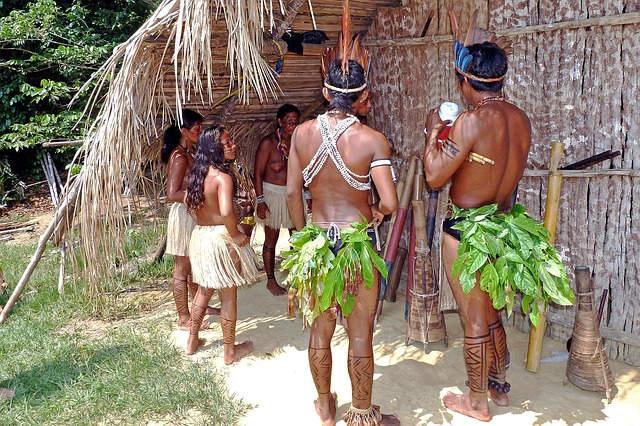 Popolo indigeno dell'Amazzonia riunito vicino ad una capanna.