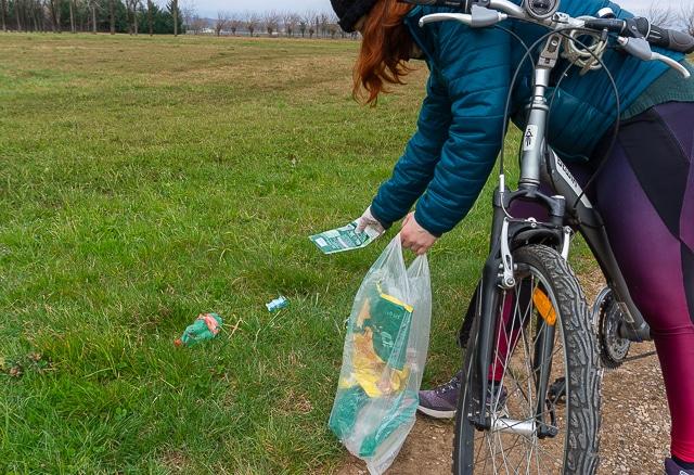 Ragazza in bicicletta che fa bike plogging raccogliendo spazzaura