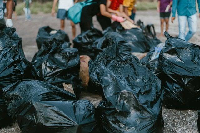 Gruppo di persone che raccoglie spazzatura in sacchi neri