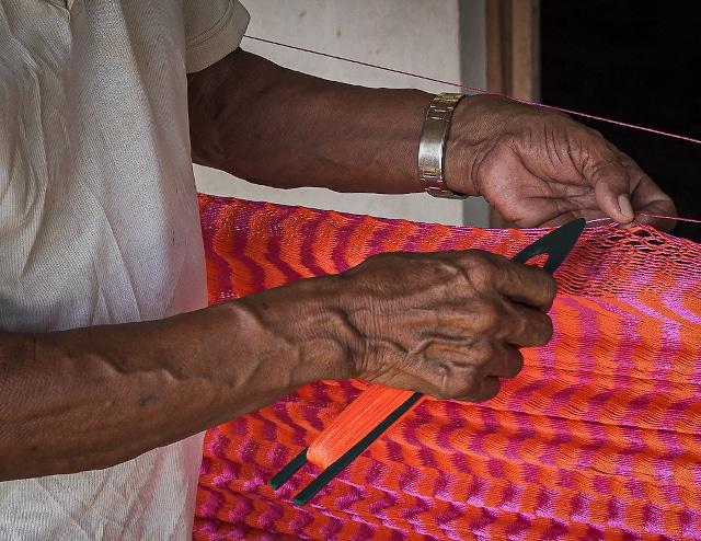 Ecoturismo nei villaggi maya. Dettaglio di mani maschili che setono un'amaca nel villaggio di ecoturismo di Tres Reye in Messico